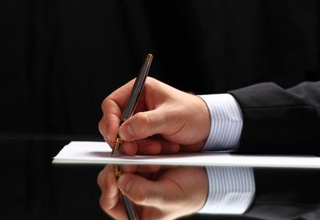 correspond�ncia: Homem que assina um documento ou correspond�ncia escrita com uma vis�o de perto de sua m�o com a caneta e folha de papel em cima de uma mesa