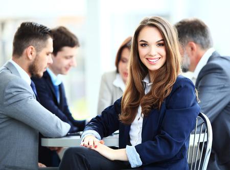 lideres: Mujer de negocios con su personal, grupo de personas en el fondo en la oficina moderna brillante en interiores