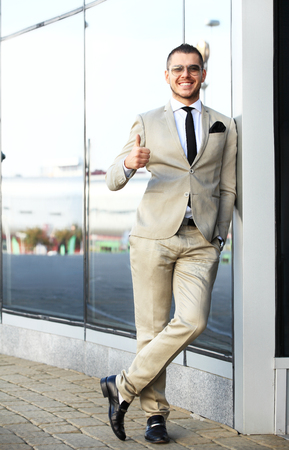 agree: Young smiling confident man doing thumbs up sign outside contemporary office building Stock Photo