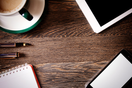 newsletter: Digital tablet computer with cup of coffee on old wooden desk. Simple workspace or coffee break with web surfing. Stock Photo