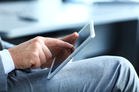 business review: Close-up image of an office worker using a touchpad to analyze statistical data