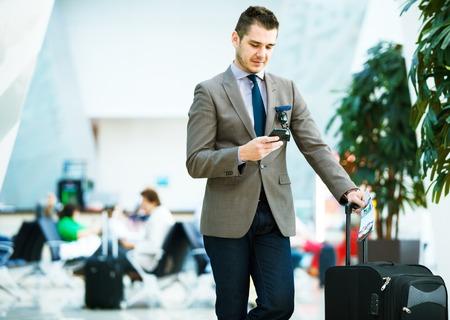 gente aeropuerto: Hombre de negocios en el aeropuerto con el teléfono inteligente y una maleta revisar el correo electrónico antes de embarcar