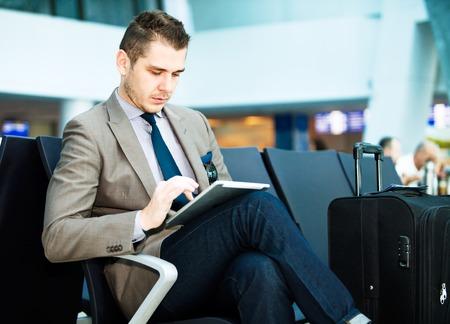 공항에서 태블릿 컴퓨터를 사용하여 현대 사업가 스톡 콘텐츠