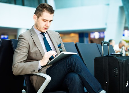 wait: modern businessman using tablet computer at airport
