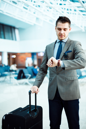 jetsetter: businessman checking time at airport