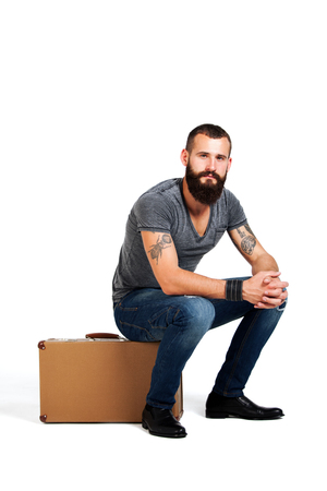 stylishly: Stylishly confident. Handsome young bearded man holding a suitcase