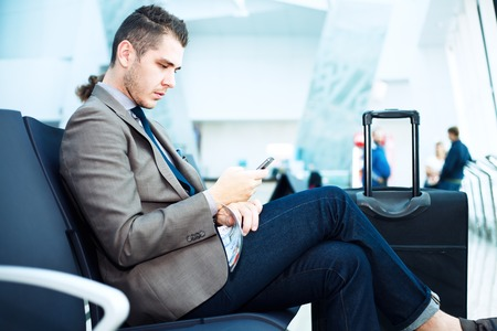 checking: Businessman at airport with smartphone and suitcase checking emails before boarding