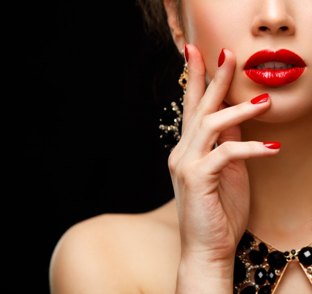 beauty skin: Red Sexy Lips and Nails closeup. Open Mouth. Manicure and Makeup. Make up concept. Half of Beauty model girls face isolated on black background