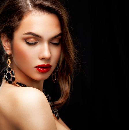 Beauty Model Woman with Long Brown Wavy Hair. Healthy Hair and Beautiful Professional Makeup. Red Lips and Smoky Eyes Make up. Gorgeous Glamour Lady Portrait. Haircare, Skincare concept photo