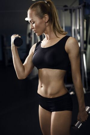 toning: Athletic young lady doing workout with weights Stock Photo