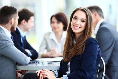 team working: donna d'affari con il suo staff, gruppo di persone in background moderno, luminoso ufficio in casa Archivio Fotografico