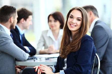 reunion de trabajo: Mujer de negocios con su personal, el grupo de personas en el fondo en la oficina moderna brillante en interiores