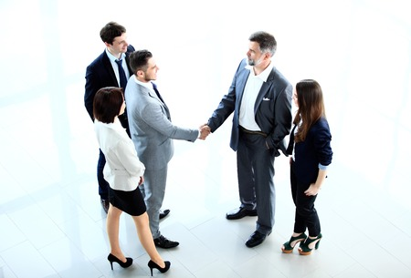 female executive: Top view of  business people shaking hands, finishing up a meeting - Welcome to business Stock Photo