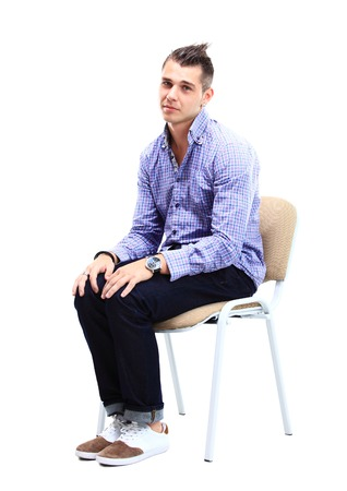 man in chair: Young caucasian handsome man sitting on the chair isolated over white background Stock Photo