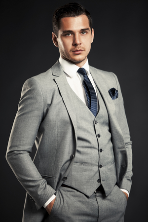 handsome man: Handsome young business man standing on black background Stock Photo