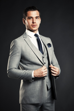 male model: Handsome young business man standing on black background Stock Photo