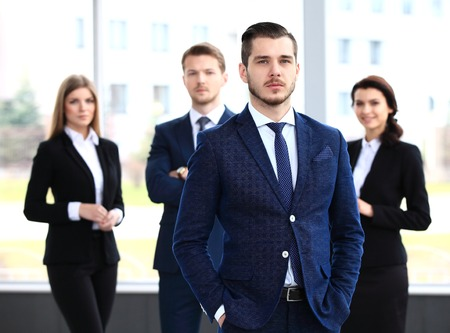 happy workers: Businessman with colleagues in the background