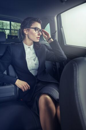 seat: Young businesswoman in back seat of car