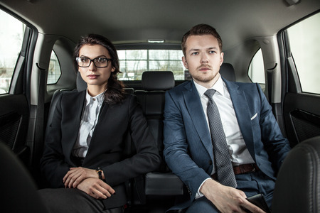 businessman and businesswoman sitting in a limousine. Young businesswoman and businessman in back seat of car