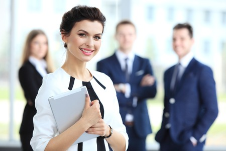 Business woman standing in foreground with a tablet in her hands her coworkers discussing business matters in the background