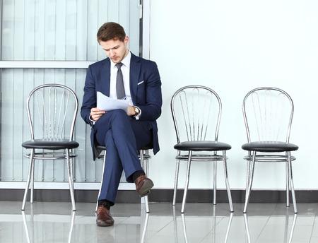 silla: Listo para la entrevista. Hombre pensativo en ropa formal que sostiene el papel mientras está sentado en la silla en la sala de espera