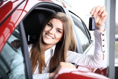 purchase: Woman Driver Holding Car Keys siting in Her New Car Stock Photo