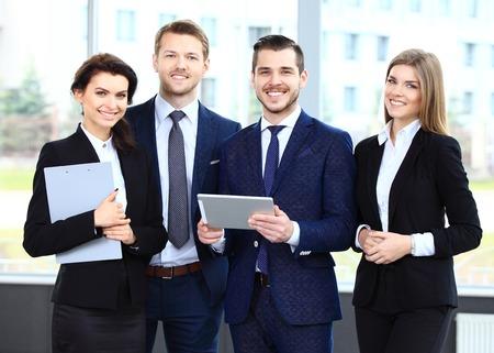 liderazgo empresarial: Feliz equipo de negocios sonriente en la oficina