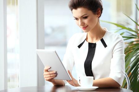 mujer pensativa: Pensativa empresaria de leer un artículo en el ordenador tableta en un café