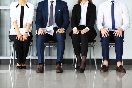 puesto de trabajo: La gente de negocios de espera para la entrevista de trabajo. Cuatro candidatos que compiten por una posici�n Foto de archivo