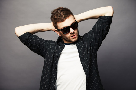 catchy: Young man in with sunglasses smiles happily with his hands behind his head.