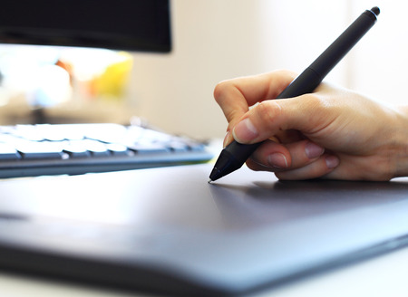 digitized: Graphic designer using digital tablet and computer in the office