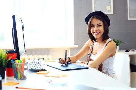 gráfico: Desenhador fêmea novo usando gráficos tablet enquanto trabalha com o computador