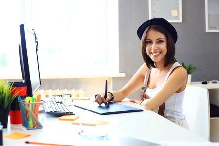 young woman sitting: Young female designer using graphics tablet while working with computer