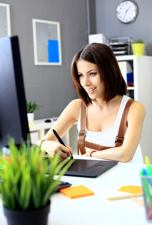 person computer: Young female designer using graphics tablet while working with computer