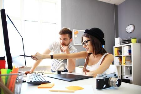 Glückliche Designer arbeiten an einem Dokument mit Kollegen hinter Arbeits
