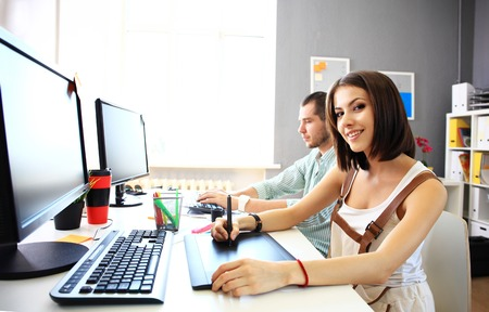 artistas: Mujer joven dise�ador que usa la tableta gr�fica mientras se trabaja con la computadora