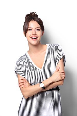 juventud: muy emocionado y feliz sonrisa mujer, joven y atractiva retrato Soporte de la muchacha dobló las manos llevan camisa, mirando a la cámara dentudo sonriente aislados sobre fondo blanco