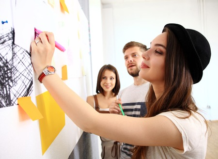 young entrepreneurs: business, people, teamwork and planning concept - smiling business team with marker and stickers working in office Stock Photo