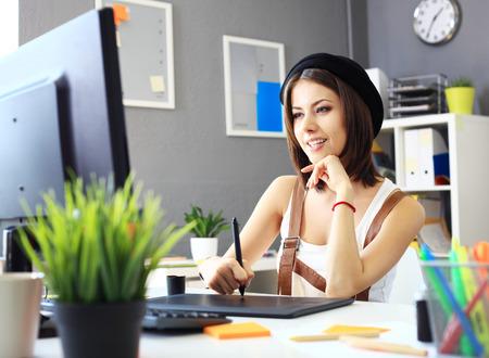 Junge weibliche Designer mit Grafiktablett während der Arbeit mit dem Computer Standard-Bild