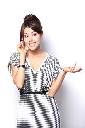amigas conversando: Mujer joven que usa un tel�fono celular aislado en blanco Foto de archivo
