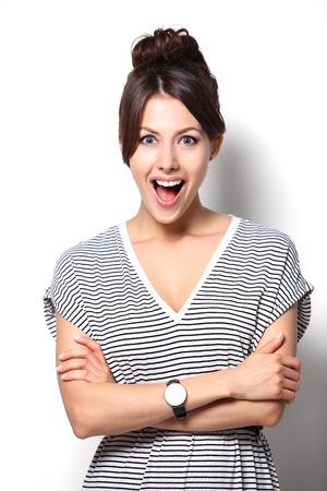 surprised: Primer plano de una mujer joven que parece sorprendida en el fondo blanco