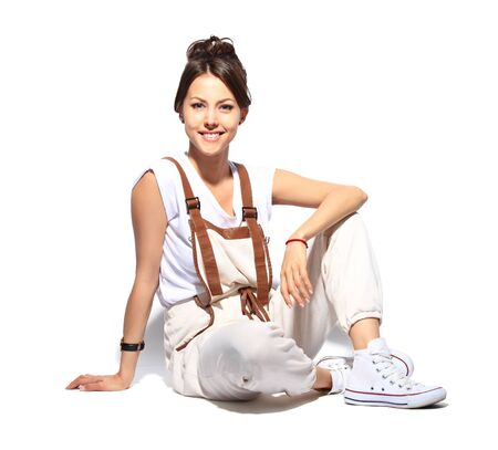 young woman sitting: Casual woman smiling sitting on the floor - isolated over a white background