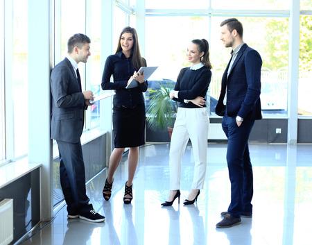 personas de pie: Colegas elegantes que se comunican en la reunión