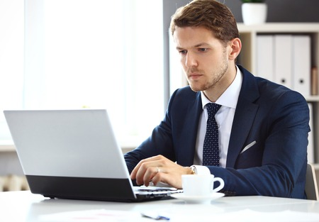 young handsome man: Handsome businessman working with laptop in office Stock Photo