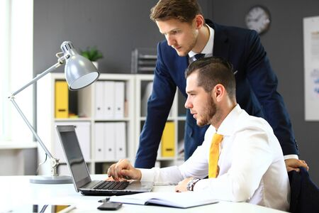 business technology: Two confident businessmen networking in office