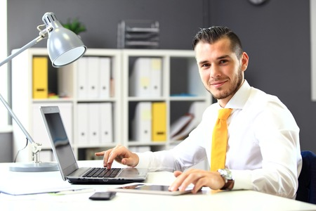 user: Handsome businessman working with laptop in office Stock Photo