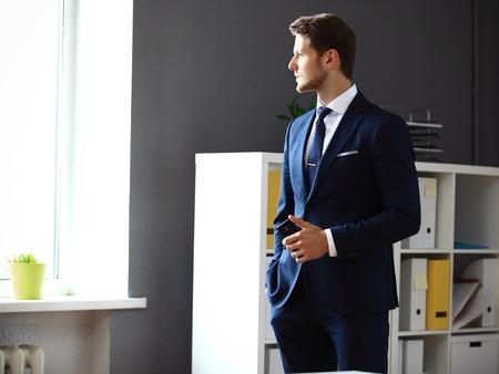 looking through window: Handsome businessman looking through window while networking in office