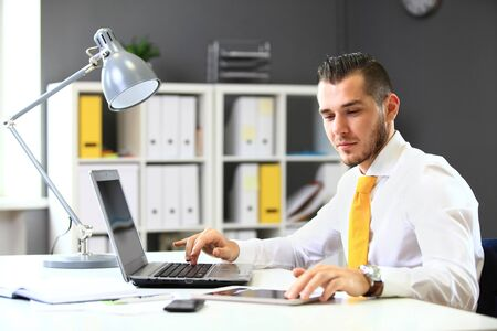 working on laptop: Handsome businessman working with laptop in office Stock Photo