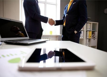 Close-shot van een tablet-computer met zakenlieden handshaking op de achtergrond