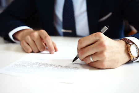 paperwork: Businessman signing a document.